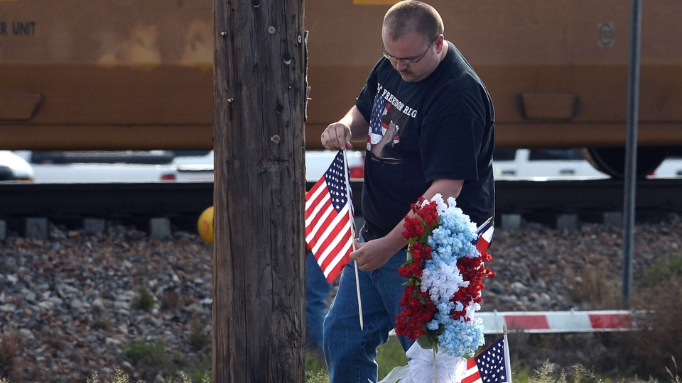 Resident Jerry Cook places a wreath his mother made and two U.S. flags at the location where a train struck a flatbed trailer carrying veterans in a parade Thursday afternoon, killing four, in Midland, Texas, Friday, Nov. 16, 2012. (AP / Odessa American, Mark Sterkel)