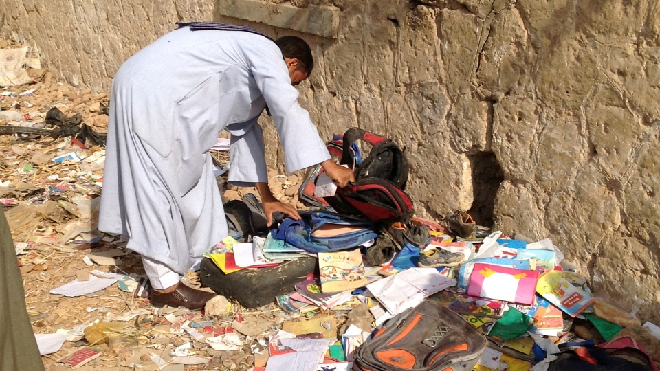 An Egyptian looks through books and school bags that were strewn along the tracks at the scene where a speeding train crashed into a bus near Assiut, Egypt, Saturday, Nov. 17, 2012.  (AP / Mamdouh Thabet)