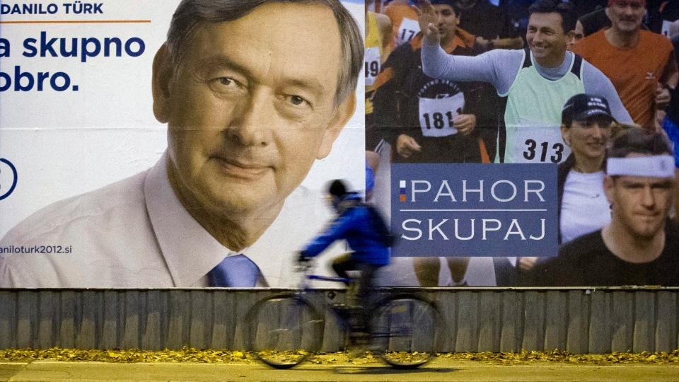 A cyclist rides past electoral posters in Ljubljana, Slovenia, Friday, Nov. 9, 2012. (AP / Darko Bandic)