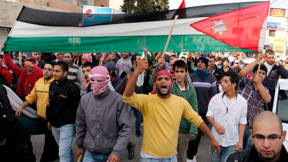 Jordanian loyalists, some armed with wooden sticks and batons to threat their critics, march in the streets while chanting pro-King Abdullah slogans and carrying a Jordanian flag in Irbid, Jordan, Friday, Nov. 16, 2012. (AP / Mohammad Hannon)