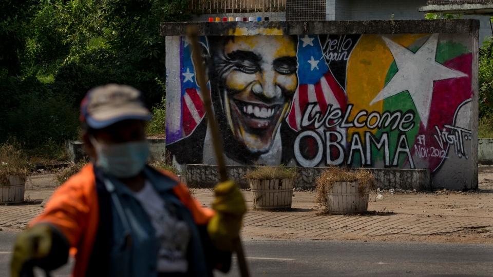 A street cleaner walks pass the graffiti welcoming U.S. President Barack Obama in Yangon, Myanmar, Saturday, Nov. 17, 2012. (AP / Gemunu Amarasinghe)