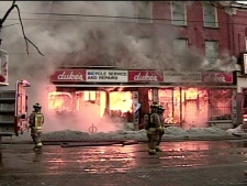 Duke's Cycle burns as firefighters work to contain the blaze on Queen Street West in downtown Toronto on Wednesday, Feb. 20, 2008.