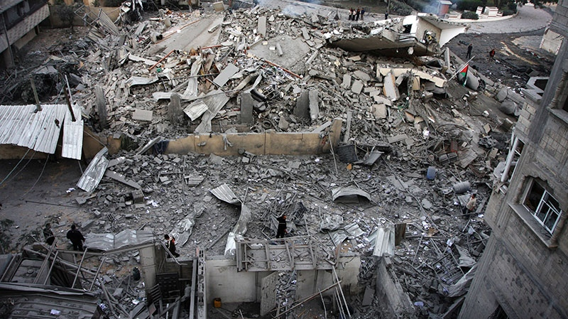 Palestinians inspect the damage at the office building of Hamas Prime Minister Ismail Haniyeh after being destroyed during an Israeli airstrike in Gaza City, Saturday, Nov. 17, 2012.  (AP / Majed Hamdan)