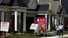 People walk past new homes that are for sale in Oakville, Ont., on Tuesday, April 14, 2009. (Nathan Denette / THE CANADIAN PRESS)