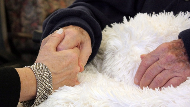 Woman holds her father's hand at Sunnybrook centre