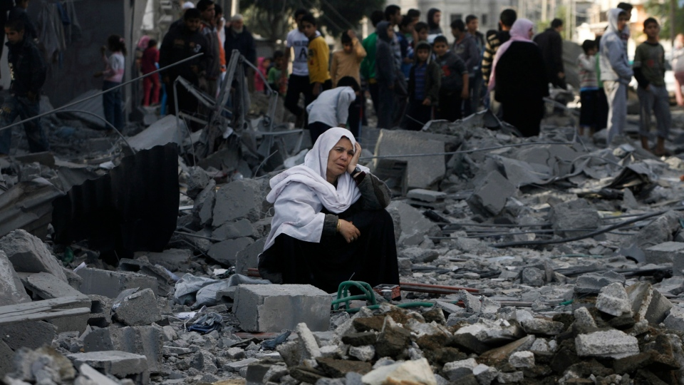 A Palestinian woman sits in rubble following an Israeli air strike in Rafah refugee camp in southern Gaza Strip, Sunday, Nov. 18, 2012. (AP / Eyad Baba)