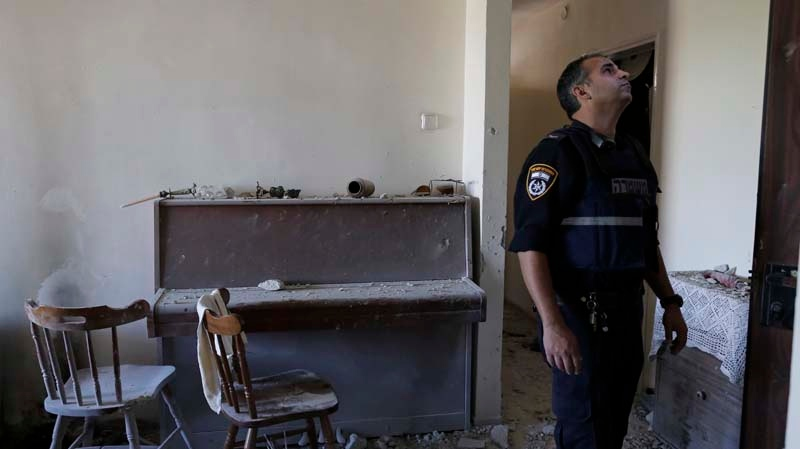 An Israeli police officer stands inside a damaged house after a rocket fired by Palestinian militants from Gaza Strip landed in Ashkelon, southern Israel, Sunday, Nov. 18, 2012. (AP / Tsafrir Abayov)