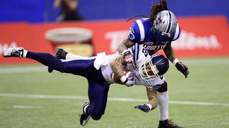 Toronto Argonauts' Chad Owens is tackled by Montreal Alouettes' Dwight Anderson during second half football action in the CFL Eastern Final Sunday, November 18, 2012 in Montreal. (THE CANADIAN PRESS / Paul Chiasson)