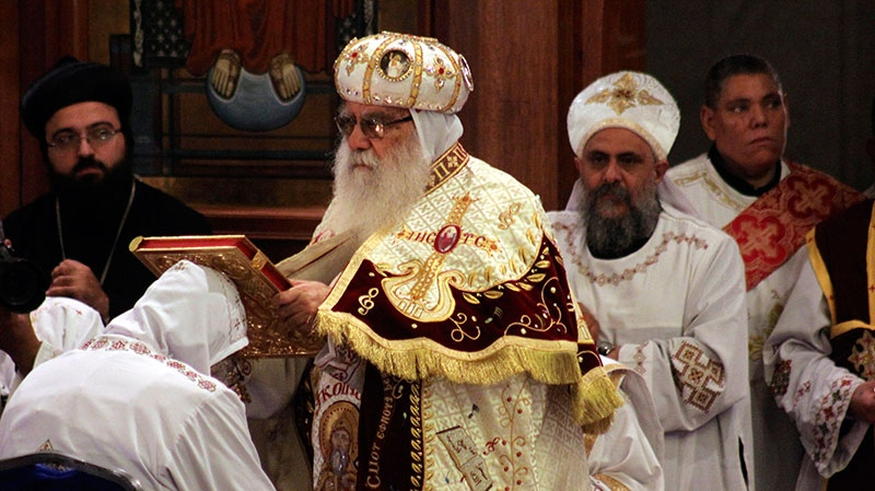 Bishop Bakhomious, the acting head of the Coptic Church, places a Bible on the head of soon to be Pope Tawadros II during an elaborate ceremony enthroning the new pope in the Coptic Cathedral in Cairo, Egypt, Sunday, Nov. 18, 2012.  (Roger Anis, El Shorouk Newspaper)