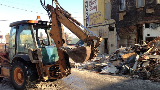 Crews worked to demolish the building that previously held Shanghai Restaurant Sunday.