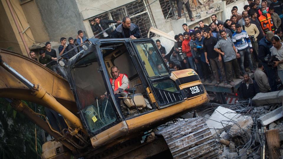 Palestinians watch bulldozers remove debris from the Daloo family house following an Israeli air strike in Gaza City, Sunday, Nov. 18, 2012. (AP / Bernat Armangue)