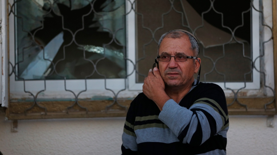 A man speaks on his mobile phone outside a damaged house after a rocket fired by Palestinian militants from inside the Gaza Strip, landed at the community of Ofakim, in southern Israel, Sunday, Nov. 18, 2012. (AP / Lefteris Pitarakis)