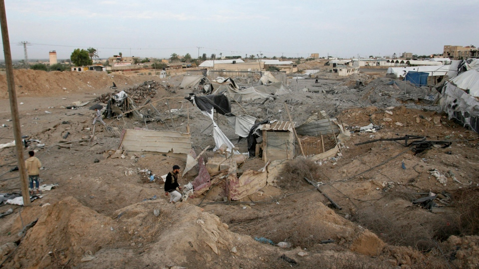 Palestinians pass by destroyed smuggling tunnels following an Israeli air strike at the border between Egypt and Rafah, southern Gaza Strip, Saturday, Nov. 17, 2012. (AP / Eyad Baba)