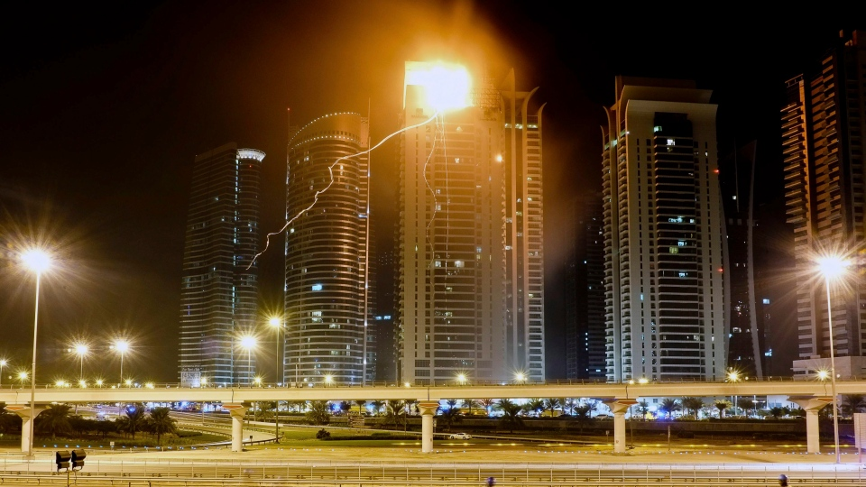 Flames come down from the rooftop of a residential tower after it caught fire in Dubai, United Arab Emirates, Sunday Nov. 18, 2012. (AP / Almoutasim Almaskery)