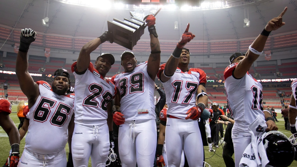 Calgary Stampeders' Stanley Bryant, from left, Brandon Smith, Charleston Hughes, Maurice Price and Marquay McDaniel celebrate with the trophy after defeating the B.C. Lions in the CFL Western Final football game in Vancouver, B.C., on Sunday, Nov. 18, 2012. (Darryl Dyck / THE CANADIAN PRESS)