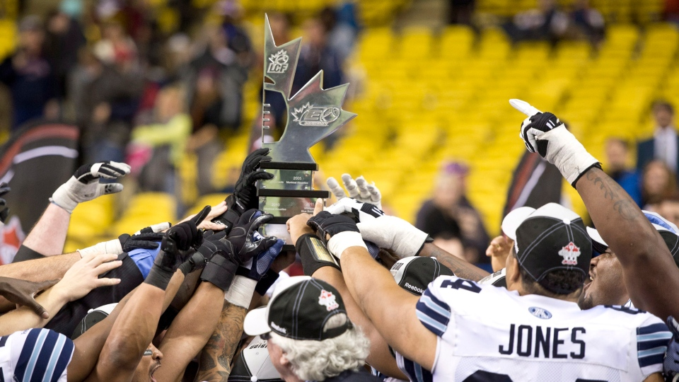 Members of the Toronto Argonauts gather around the division trophy after beating the Montreal Alouettes in the CFL Eastern Final in Montreal, Sunday, Nov. 18, 2012. (Paul Chiasson / THE CANADIAN PRESS)