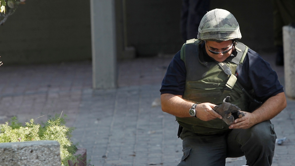 An Israeli police sapper collects the remains of a ordnance fired by Palestinian militants from the Gaza Strip that landed in the southern Israeli town of Ashkelon, Monday, Nov. 19, 2012.  (AP / Tsafrir Abayov)