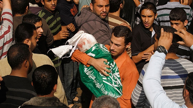 A Palestinian man holds the body of 11-month old baby Ibrahim Daloo during a funeral for at least eleven members of the Daloo family in Gaza City, Monday, Nov. 19, 2012. At least eleven members of the Daloo family were killed on Sunday when an Israeli missile struck the two-story home of the family in a residential area of Gaza City. (AP Photo/Hatem Moussa)