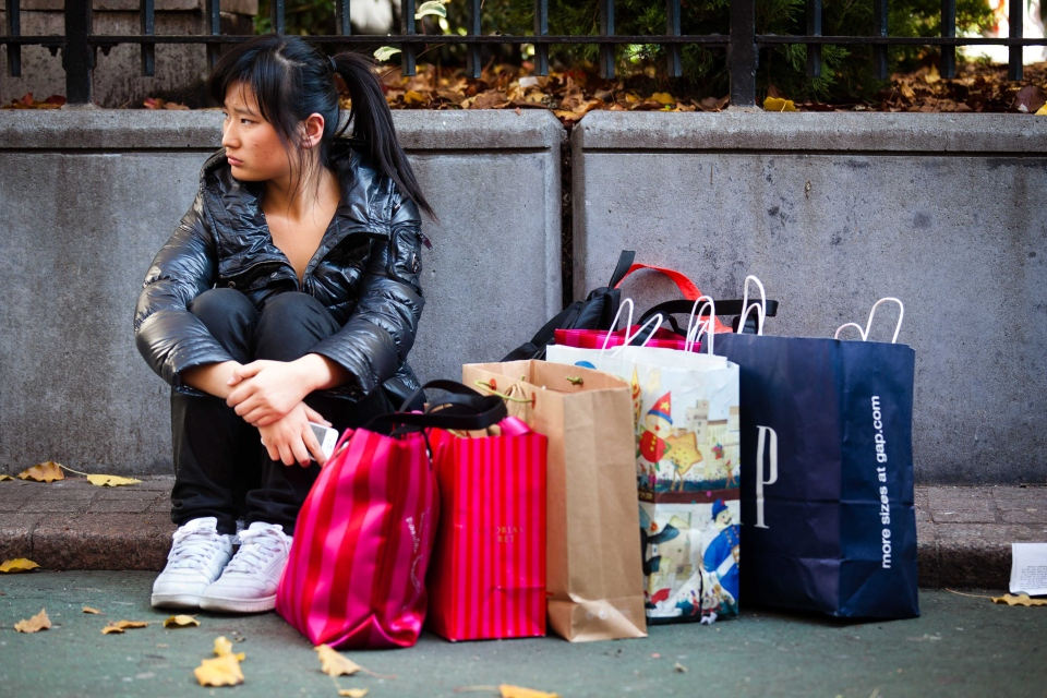 A shopper rests herself and her bags in New York during the busiest shopping day of the year in this Nov. 25, 2011. (AP / John Minchillo)