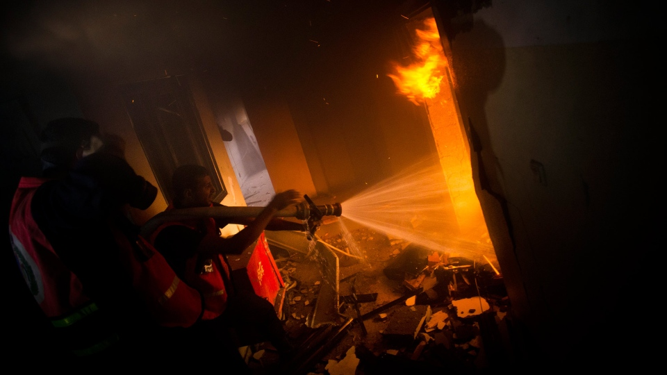 Palestinians firefighters try to extinguish a fire after an Israeli strike on a building of Gaza City, Monday, Nov. 19, 2012. (AP / Bernat Armangue)