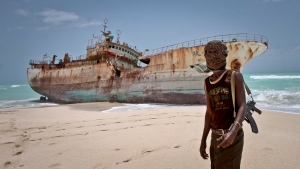 Masked Somali pirate Abdi Ali stands near a Taiwanese fishing vessel that washed up on shore after the pirates were paid a ransom and released the crew, in the once-bustling pirate den of Hobyo, Somalia on Sunday, Sept. 23, 2012.  (AP / Farah Abdi Warsameh)
