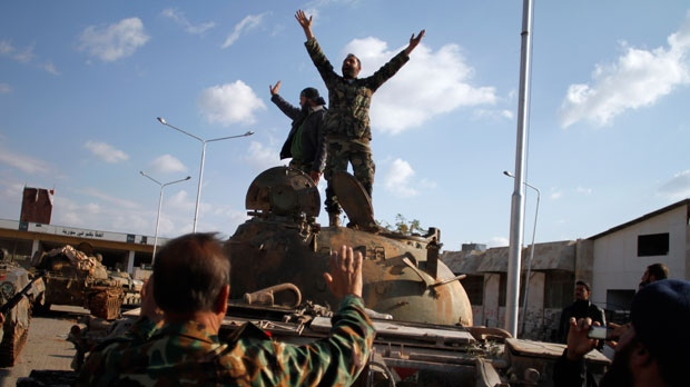 Syrian fighters celebrate a victory on top of a tank they took after storming a military base in Aleppo on Monday, Nov. 19, 2012. (AP / Khalil Hamra)