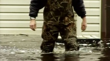 A man wades through knee-high flood water that surrounds his home in Upper Clyde, N.S., on Tuesday, Nov. 9, 2010.