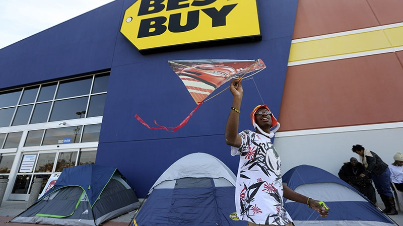 Hakkius Smith, 16, tries to catch wind and fly a kite in front of a Best Buy store where his family is camped out in Cockrell Hill, Texas, Monday, Nov. 19, 2012. (AP / LM Otero)