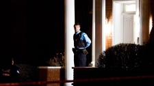A police officer guards the entrance of the house of reputed mafia boss Nicolo Rizzuto Sr., who was reportedly gunned down in his home in Montreal, Wednesday, Nov. 10, 2010.(Graham Hughes / THE CANADIAN PRESS)