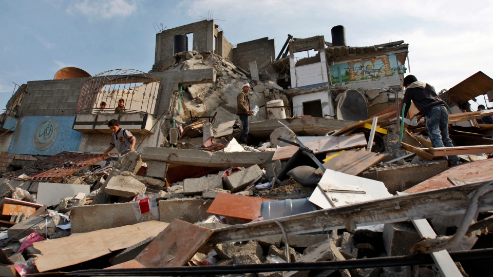 Palestinians climb on the rubble at the destroyed house of Islamic Jihad militant Hasam Al Kholy, hit overnight in an Israeli strike on Gaza City, Tuesday, Nov. 20, 2012. (AP / Adel Hana)