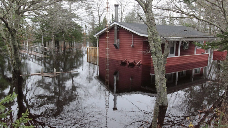 A cottage along the Clyde River in South Western Nova Scotia on Tuesday, November 9, 2010, is partly submerged as flood waters continue to surge after several days of heavy rain hit the province. (THE CANADIAN PRESS/Mike Dembeck)