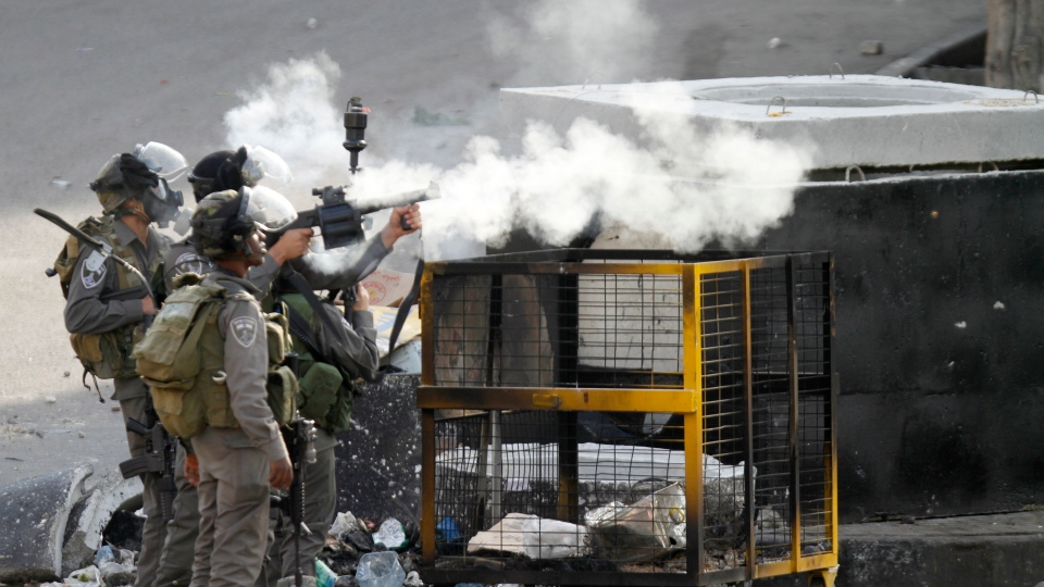 An Israeli border policeman fires a tear gas canister during clashes against Israel's operations in the Gaza Strip in the West Bank city of Hebron on Tuesday, Nov 20, 2012.(AP / Nasser Shiyoukhi)