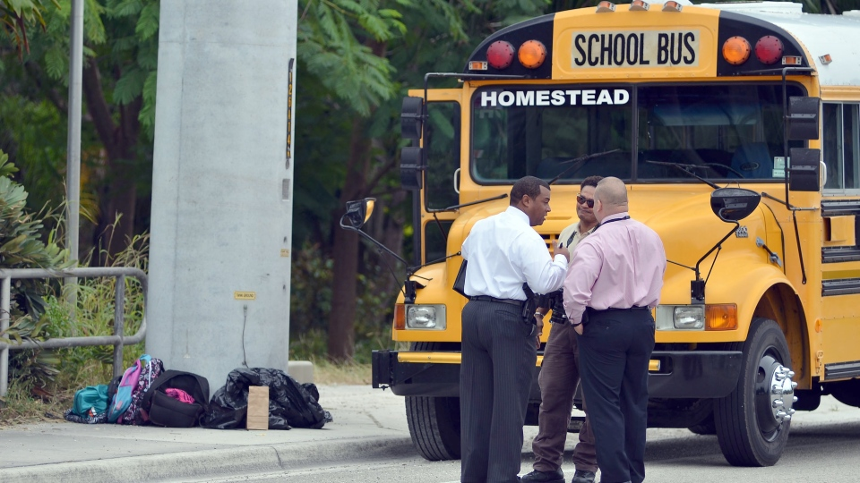 Police investigators stand outside a school bus after a child was shot in Homestead, Fla., on Tuesday, Nov. 20, 2012. (El Nuevo Herald, Gaston De Cardenas)