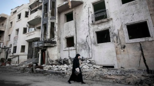 In this Saturday, Nov. 17, 2012 photo, a Syrian woman walks in front of a destroyed hospital where heavy clashes took place between rebel fighters and the Syrian army to seize control over the area, on the outskirts of Aleppo, Syria. (AP Photo/Narciso Contreras)