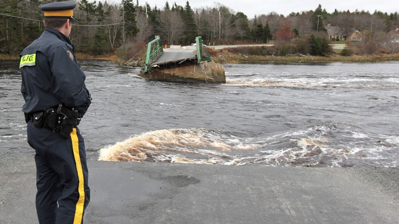 A member of the RCMP looks over the Tusket River bridge along Highway 3 in Tusket, Nova Scotia on Wednesday, November 10, 2010. (Mike Dembeck / THE CANADIAN PRESS)