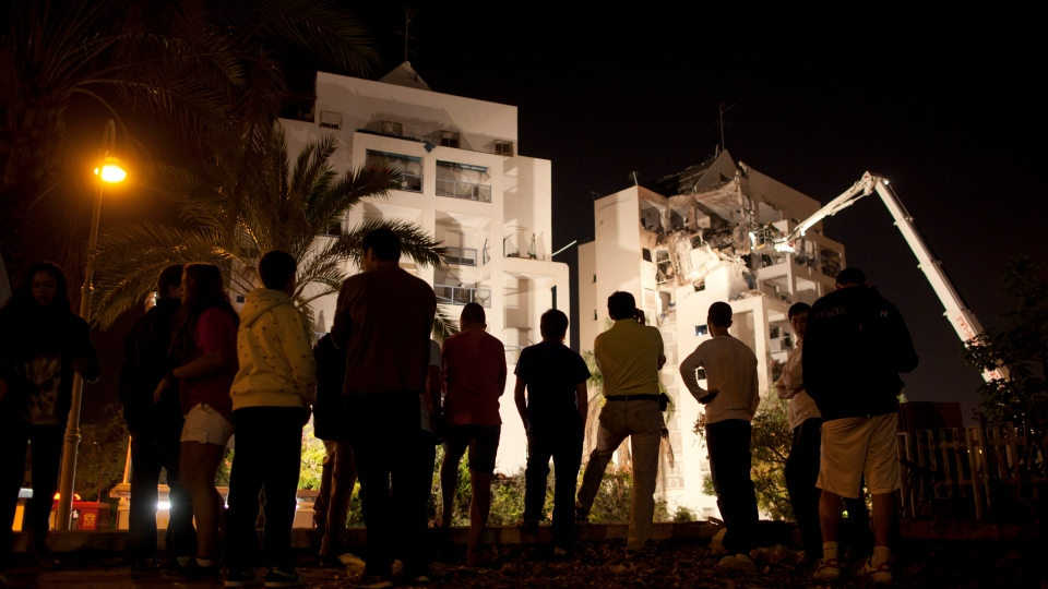 Israelis inspect damage at an apartment building after it was hit by a rocket fired by militants from Gaza Strip in Rishon Lezion, Israel, Tuesday, Nov. 20, 2012. (AP / Oded Balilty)