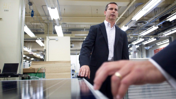 Dalton McGuinty with a solar module, Aug. 4, 2011.