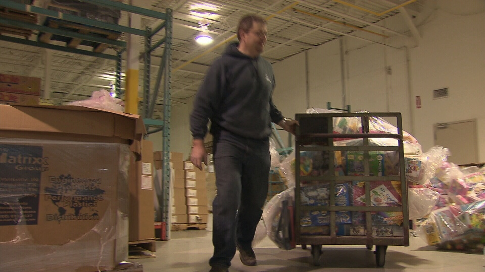 A Salvation Army warehouse worker handles toys after an internal audit revealed millions of dollars worth of toys have gone missing.