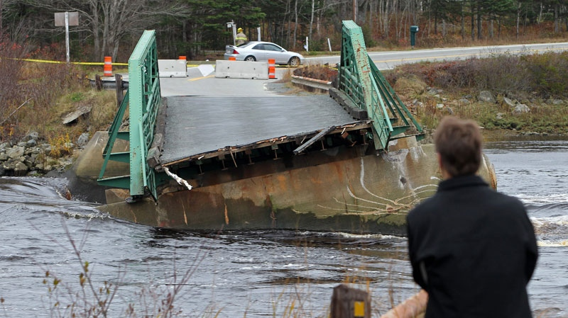 A bystander looks over the Tusket River bridge along Highway 3 in Tusket, Nova Scotia on Wednesday, November 10, 2010. (Mike Dembeck / THE CANADIAN PRESS)
