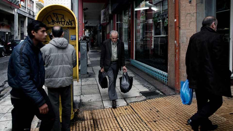 People walk in central Athens, on Wednesday, Nov. 21, 2012. (AP / Petros Giannakouris)