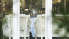 A bullet hole is framed by tree branches in the backyard window of Nicolo Rizzuto's Montreal home is shown on Thursday Nov. 11, 2010. (Peter Ray Rakobowchuk / THE CANADIAN PRESS)