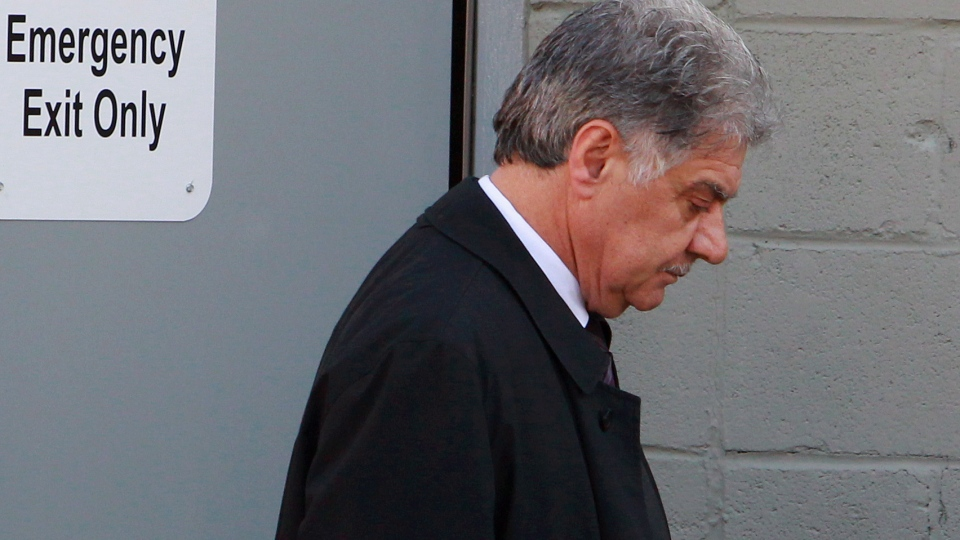 Joe Fontana leaves from the emergency exit door of his lawyer Gord Cudmore's office after making a statement about charges he is facing after an RCMP investigation, in London, Ont., Thursday, Nov. 22, 2012. (Dave Chidley / THE CANADIAN PRESS)