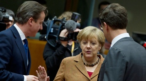 British Prime Minister David Cameron, left, speaks with German Chancellor Angela Merkel, centre, and Dutch Prime Minister Mark Rutte during a round table meeting at an EU summit in Brussels on Thursday, Nov. 22, 2012. (AP / Yves Logghe)