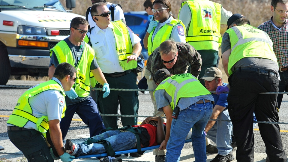 Emergency workers carry a victim across the Interstate 10 median after a massive auto accident in southeast Texas, Thursday, Nov. 22, 2012. (The Beaumont Enterprise, Guiseppe Barranco)
