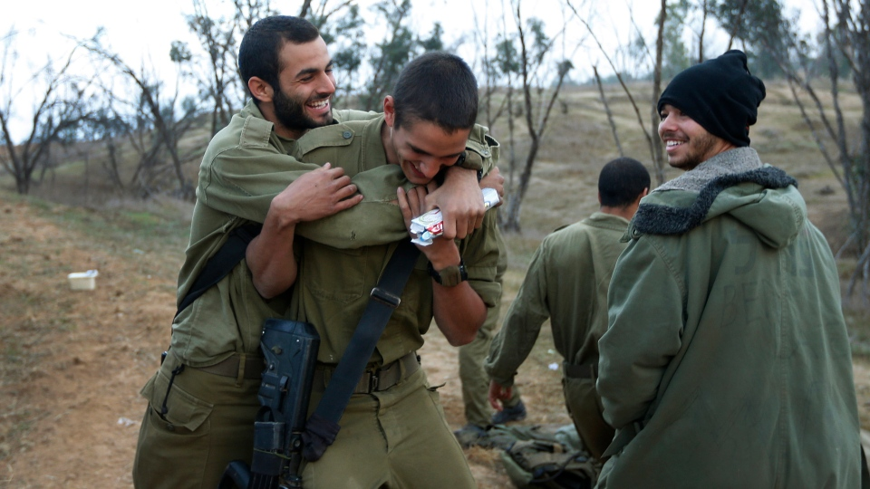 An Israeli soldier hugs a comrade on his birthday near the Israel Gaza Strip Border, southern Israel, Thursday, Nov. 22, 2012. (AP / Lefteris Pitarakis)