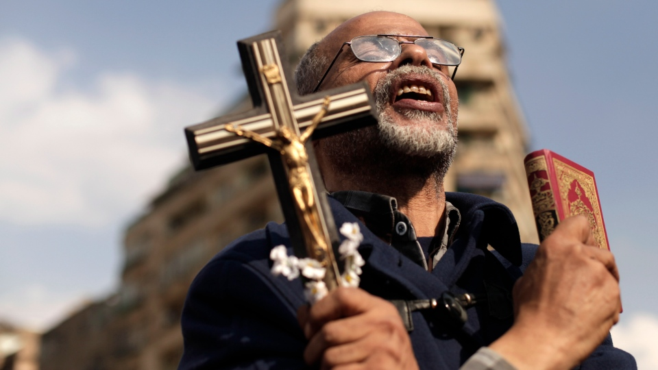 An Egyptian protester chants slogans and holds a cross and a Quran in Tahrir Square, Friday, Nov. 23, 2012. (AP / Maya Alleruzzo)