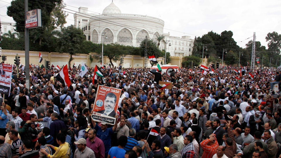 Supporters of Egyptian President Mohammed Morsi chant slogans and wave his campaign posters outside the Presidential palace, background, in Cairo, Egypt, Friday, Nov. 23, 2012. (AP  / Ahmed Abd el Fatah)