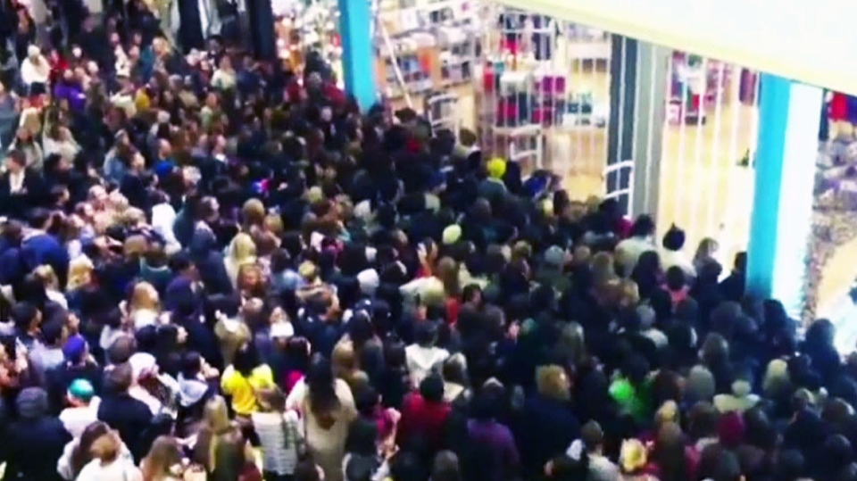 A massive crowd swarms into a store as Black Friday kicks off in the U.S. Friday, Nov. 23, 2012.