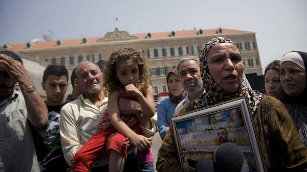 Samira Rahmoon, right, carries a picture of her husband Lebanese TV psychic Ali Sibat who was arrested by the Saudi religious police in May 2008 and sentenced to death last November on charges of practicing witchcraft, as she speaks to reporters during a sit-in in front of the Government House in Beirut, Lebanon, Friday, June 11, 2010. (AP / Grace Kassab)