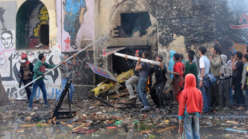 Egyptian protesters opposed to president Mohammed Morsi try to breach a building used by Morsi supporters during clashes near Tahrir Square in Cairo, Egypt, Friday, Nov. 23, 2012. (AP / Mohammed Asad)